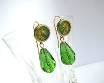 Golden earrings with miniature painting of a seahorse