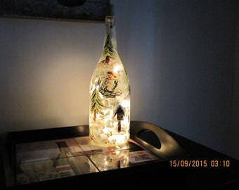 Wine Bottle with hand painted snowman dressed in red hat red scarf surrounded by trees and birdhouse. White lights inside the wine bottle.