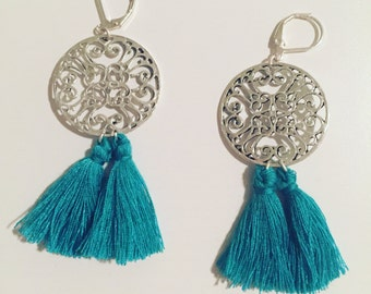 Ornate dangling earrings of two turquoise tassels