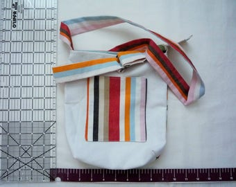 Small cross-body bag in white denim with bold canvas stripes, multiple pockets, adjustable strap