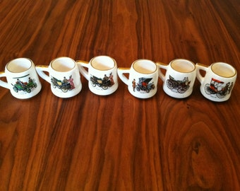 Six Historical Porcelain SHOT CUPS/MINI-Mugs with gold trim and early Wagon Scenes.