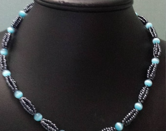 Four strand gunmetal silver and turquoise glass cat's eye necklace