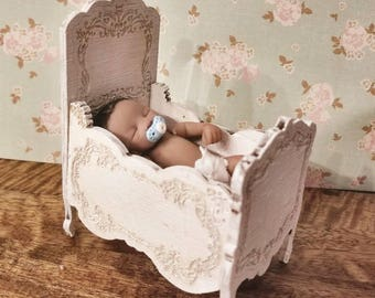 Miniature dollhouse crib with delicate detailing and finished in an antique chalky french white 1:12 scale