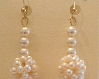 Ball of cultured pearls with Swarovski pearls dangle on 14 karat gold ear latches.