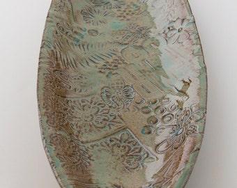 Long oval green serving platter on dark clay