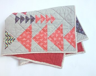 Modern flying geese on grey quilt. Colors are coral red, grey, white, navy blue.