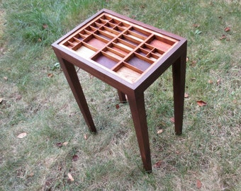 Walnut end table with flush tapered legs and a colorful top made of different wood inlays within a reclaimed printer's type box.