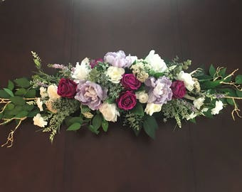 Wedding arch decoration, purple, gold and white wedding flowers.