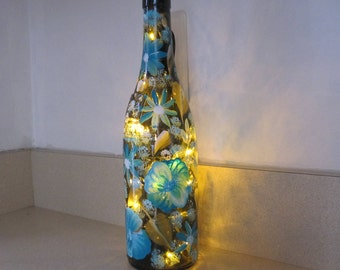 On Sale Wine bottle with aqua blue and white pansies green leaves as well as aqua blue and white baby breath lights inside