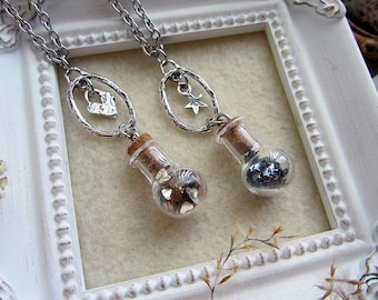 Magical potion necklaces made with glass vials filled with glitter and sterling silver dangling star & heart pendants. Custom length chain.