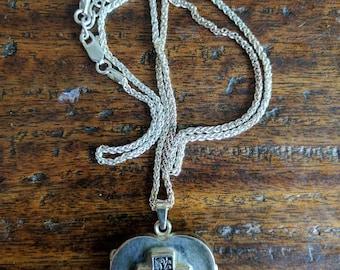 Heart shaped silver locket with flower cross