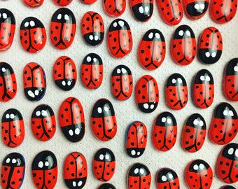 70 hand-painted glass ladybirds, gadget for shop customers. Small gift representing sales firm. Thought brings luck