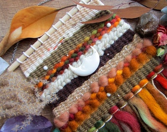 "Bohemian woven tapestry wall hanging in earthy / Autumn colors with carved crescent, white howlite, and silver beads.  Size 7"" x 15"""