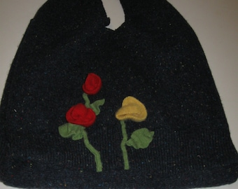 Upcycled felted wool bag, decorated with red and yellow flowers with green stems and leaves.