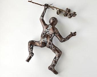 Climbing man sculpture on a tree branch, rustic wall decor, contemporary art, interior design, decorative art