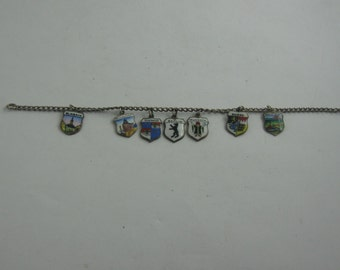 Charm bracelet: bracelet in silver (Ag 835) with 7 crest pendants made of silver (Ag 800) and enamel. Length approx 17.7 cm. VINTAGE