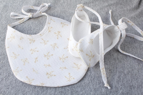 white floral bib and baby girl shoes