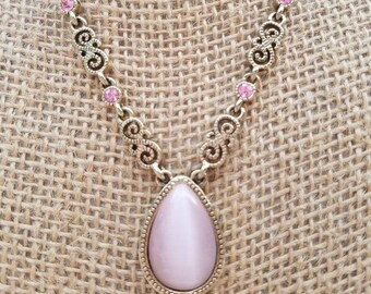 Darling gold tone and pink crystal necklace featuring a tear drop cats eye
