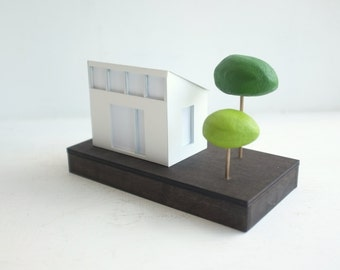Modern lighted paper house - contemporary design ghost house - white paper architecture with two green trees - geometric structure