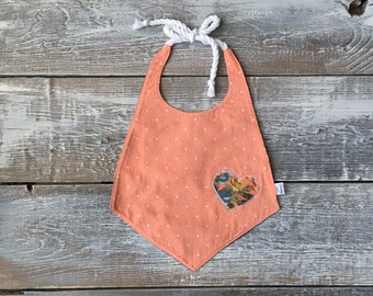 Peach baby bib with heart appliqué