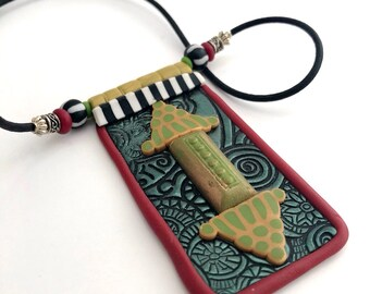 Pendant with applied design in middle eastern or African flavor, made by Marie Segal 2006
