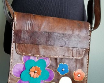 Raw cowhide messenger cross-body bag with hand painted flowers and leather cutouts flowers.