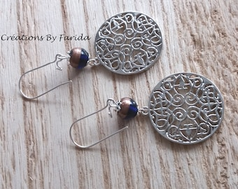 Earrings with round Celtic stamp and a blue and gold bead