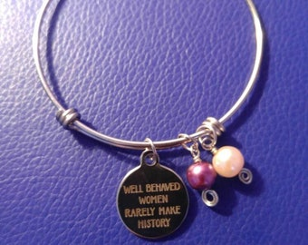 Silver feminist bangle with purple and white bead.