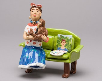 Ceramic / clay hand built sculpture of Frida Kahlo with monkey, painting, paint brush and paint palet sitting of a sofa.all in miniature.