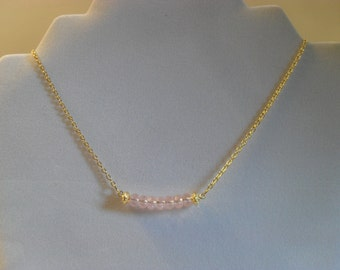 Girly and sophisticated pink faceted rondelle and gold-plated filigree bar necklace