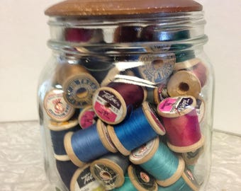 Glass jar with wooden lid full of wooden thread spools
