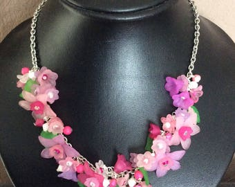 Halsketing with lucite flowers, pinks and green leaves