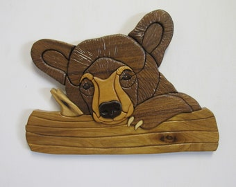Intarsia bear cub on branch