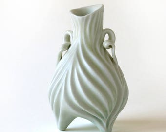 Small porcelain bud vases in creamy pale yellow, carved with curvy grooves
