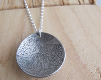 Sterling silver petal necklace, oval domed disc with oxidised petal detail.