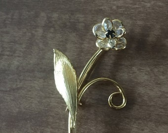 Golden flower broche with black center stone