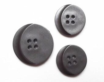Trio of metallic grey buttons acrylic