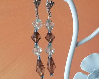 Brown and clear crystal like bead earring with design at ear.