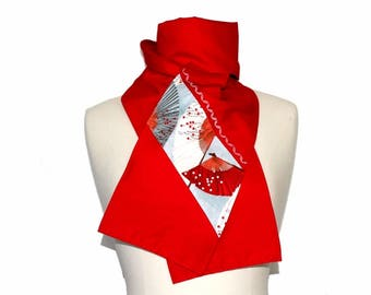 A scarf made of red cotton enhanced with grey fans