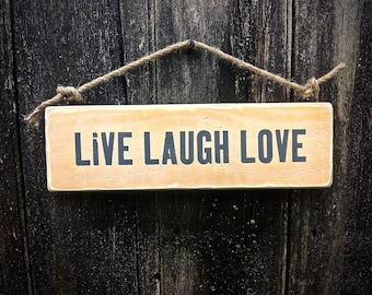 Handmade wooden sign with the words 'live, laugh, love'.