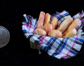 Assortment of bread in a basket w/plaid cloth