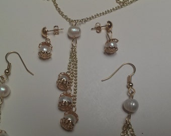 Set of necklace and earrings with three strands of freshwater pearls each on gold chains, plus single pearls for earrings.