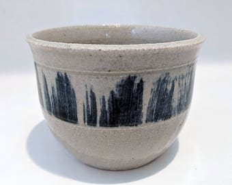 Beige porcelain cup with dark blue brush strokes
