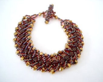 Red Gold Beaded Flat Spiral Bracelet hand beaded with red cross, gold metallic bicone, and iridescent red seed beads
