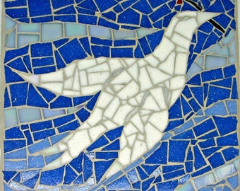 White dove of peace handmade mosaic, flying blue sky, holding a red flower