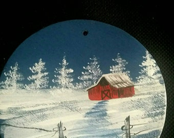 Hand painted wide mouth mason jar lid with a snow scene and red barn
