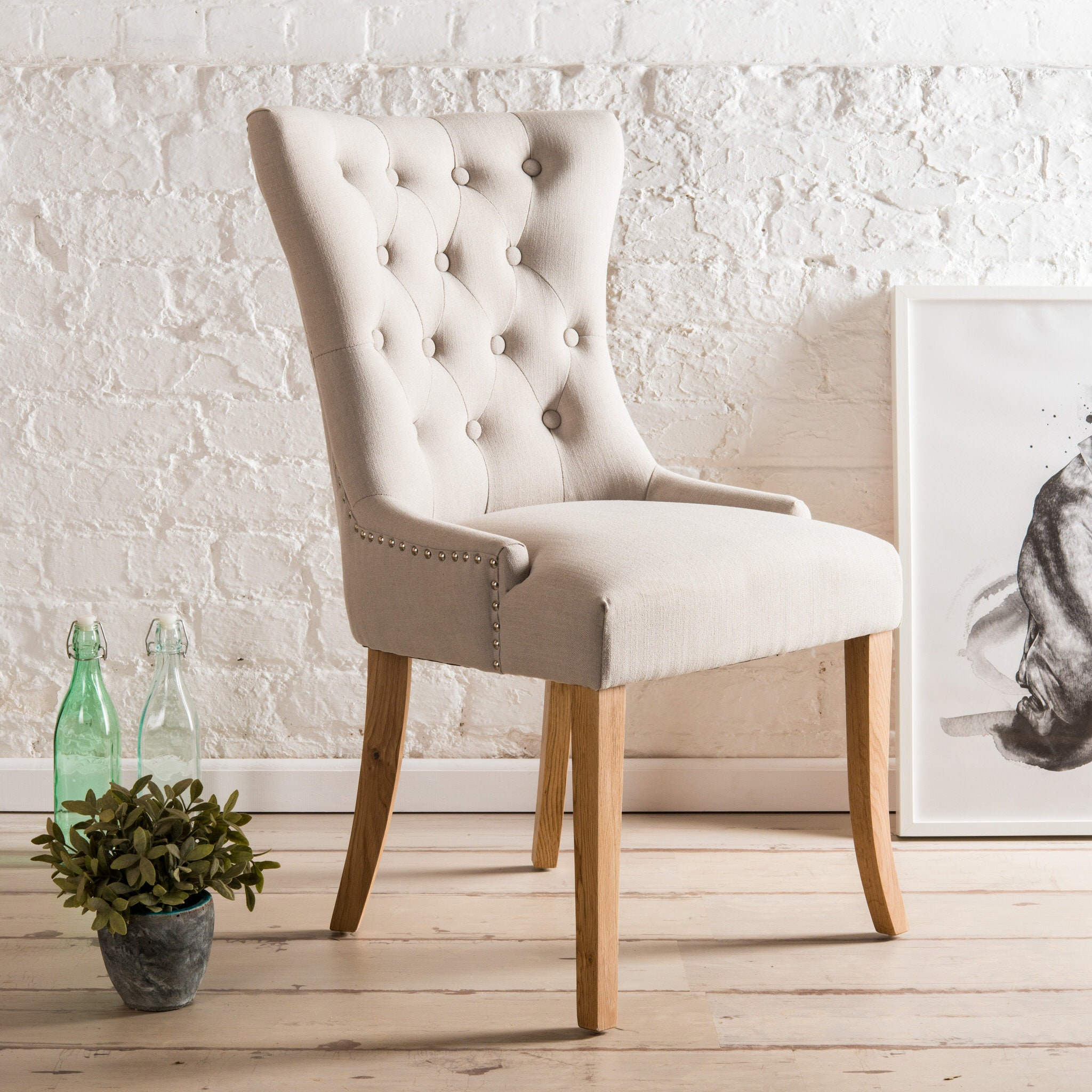 Alma wing back Upholstered Dining Chair with button back and chrome knocker. Light grey or dark grey