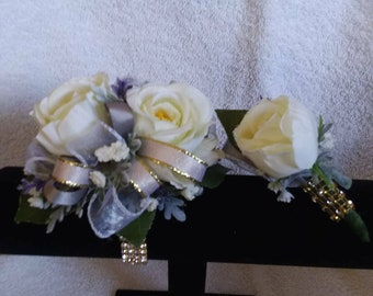 Gold rhinestone wrist corsage and matching boutonnière set made with realistic-looking antique white roses, with white and gold ribbon.
