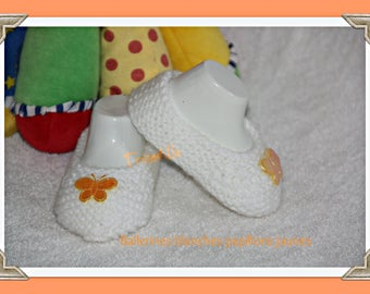Pair of white ballerina slippers decorated with a butterfly