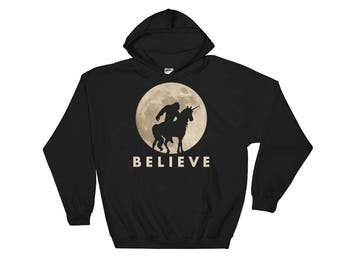 Bigfoot Riding a Unicorn Against a Full Moon Hoodie, Believe!